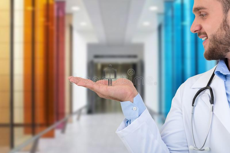 Portrait of a smiling male doctor holding xray symbol in hands. royalty free stock images