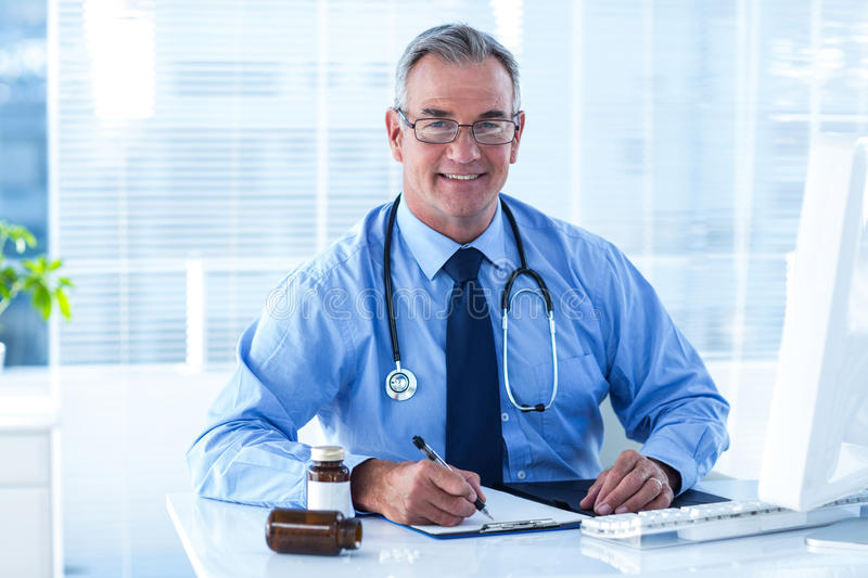 Portrait of smiling male doctor writing on document in clinic royalty free stock photos