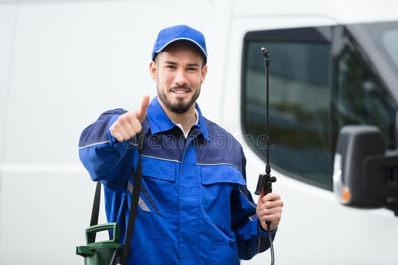 Portrait Of A Smiling Male Pest Control Worker. Standing In Front Of Vehicle stock photography