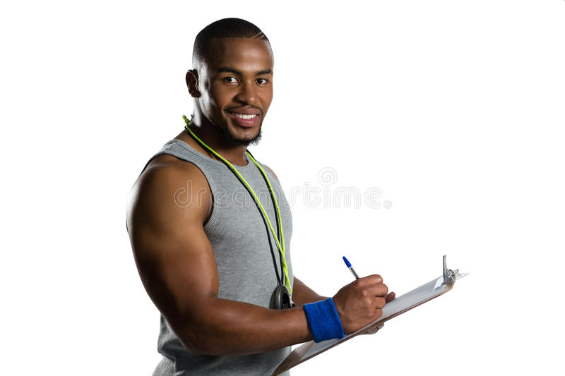 Portrait of smiling male rugby coach writing on clipboard royalty free stock images