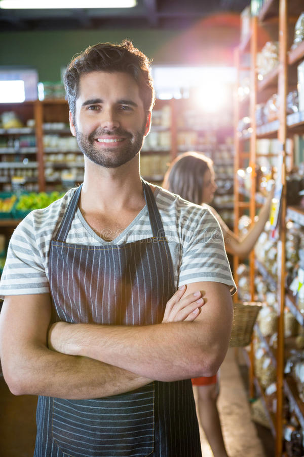 Portrait of smiling male staff standing with arms crossed in organic section. Of super market royalty free stock image