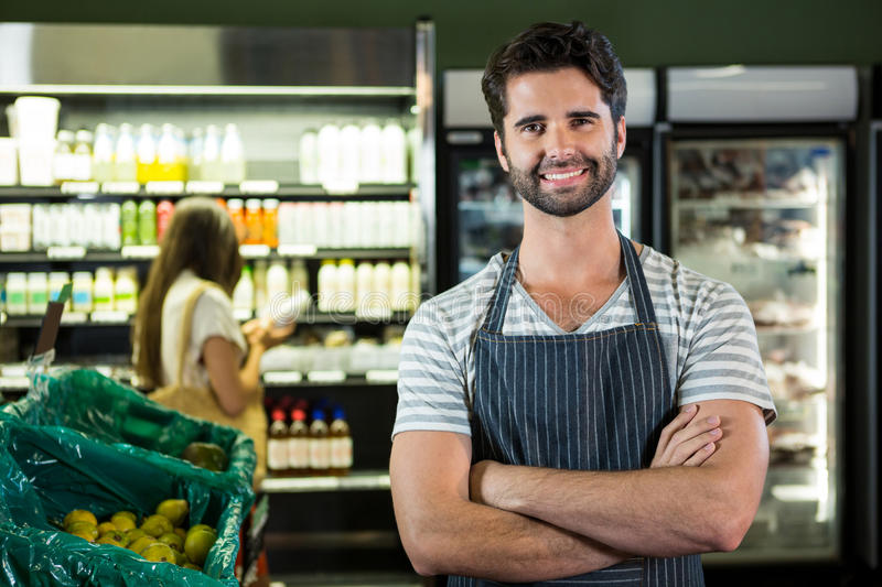 Portrait of smiling male staff standing with arms crossed in organic section. Of super market royalty free stock images