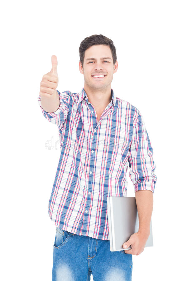 Portrait of smiling male student holding a laptop and showing a thumbs up. On white background royalty free stock images