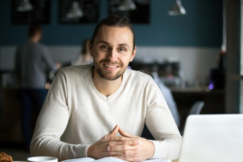 Portrait of smiling male student studying out in cafe. Portrait of smiling millennial men sitting in cafe with laptop and books on table, happy young guy work in stock photography