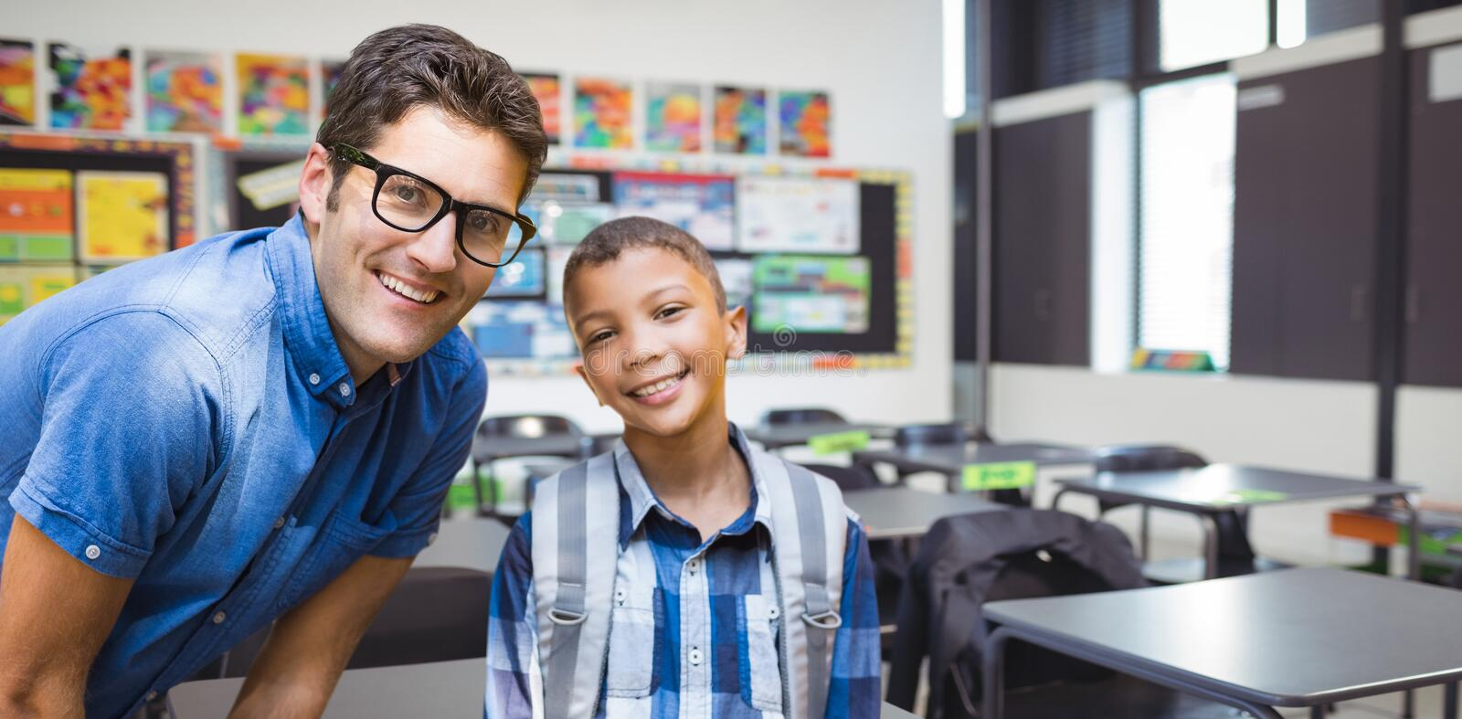 Composite image of portrait of smiling male teacher with student. Portrait of smiling male teacher with student against interior of empty classroom royalty free stock photos