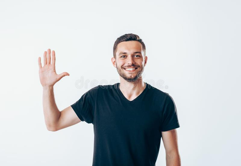 Portrait of smiling man with hand raised in greeting royalty free stock photo