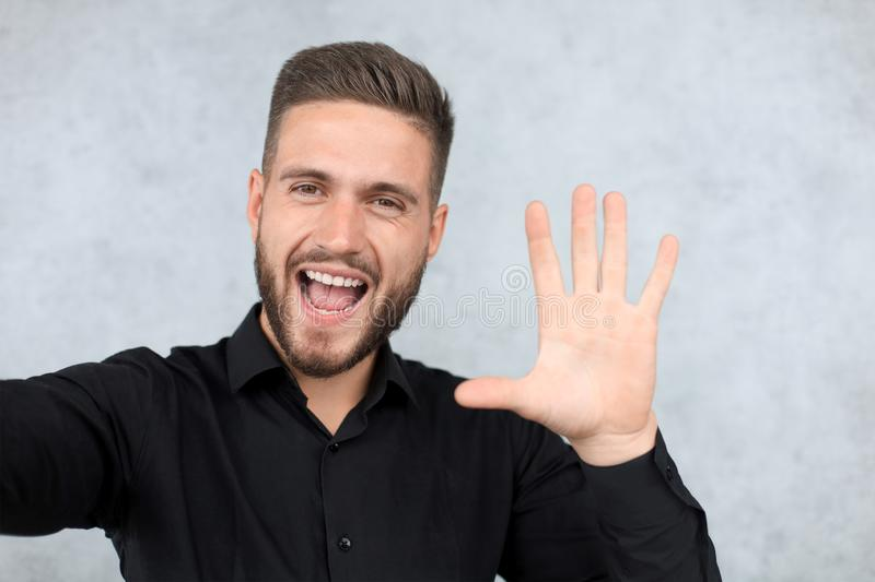 Portrait of smiling man with hand raised in greeting. High five concept stock photo