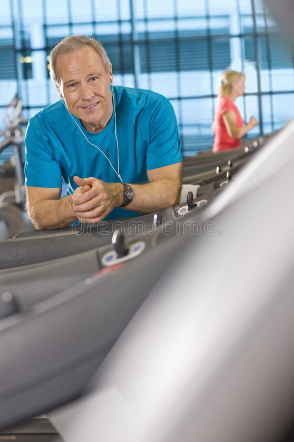 Portrait of smiling man with headphones leaning on treadmill in health club. Portrait of smiling men with headphones leaning on treadmill in health club stock image