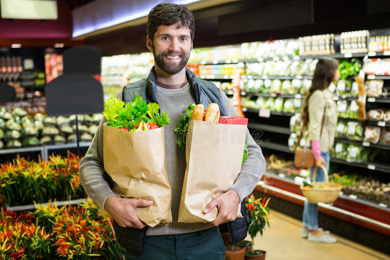 Portrait of smiling man holding a grocery bag in organic section. Portrait of smiling men holding a grocery bag in organic section of supermarket stock image