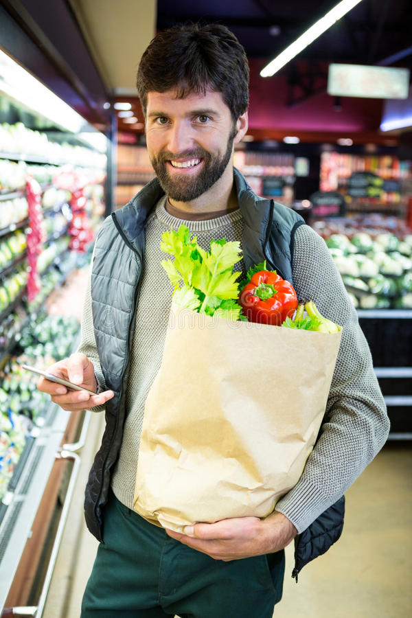 Portrait of smiling man holding a grocery bag in organic section. Of supermarket stock photos
