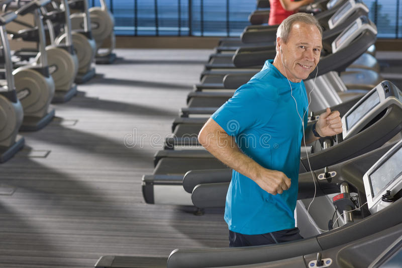 Portrait of smiling man listening to music on headphones and running on treadmill in health club. Portrait of smiling men listening to music on headphones and stock photo