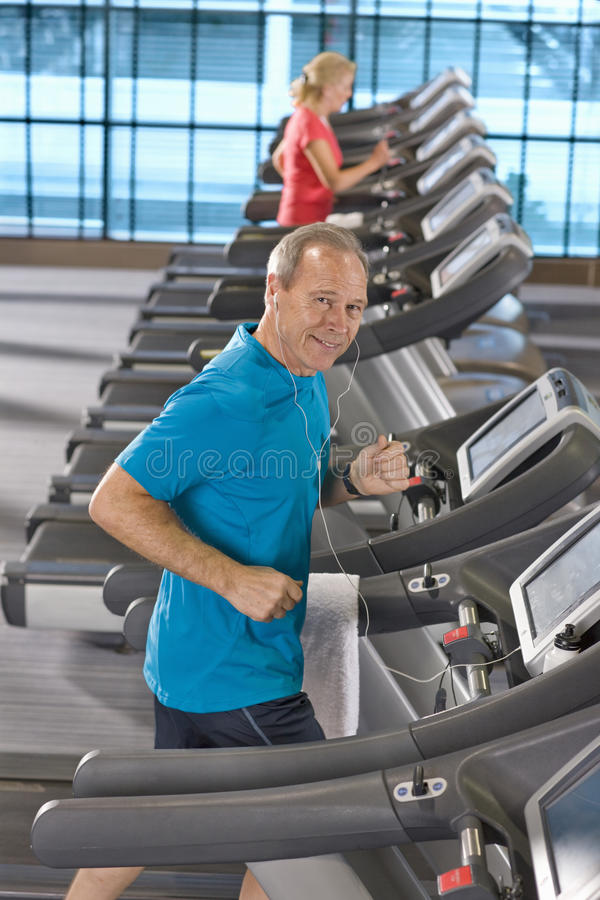 Portrait of smiling man listening to music on headphones and running on treadmill in health club. Portrait of smiling men listening to music on headphones and stock photos