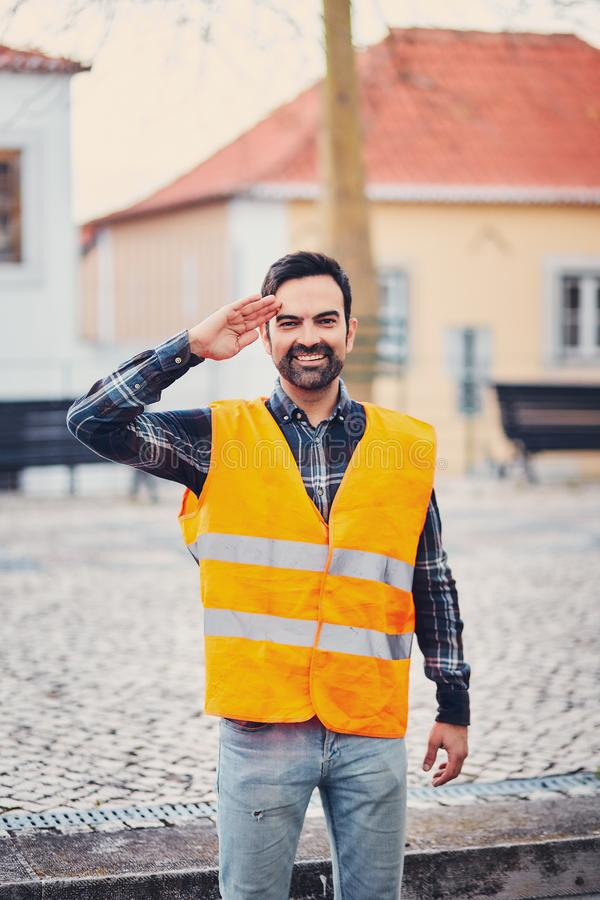 Portrait of a smiling man in an orange life jacket on the street salutes with a hand to his head. A young man with a beard jokes s. Alute. A life jacket should royalty free stock photography