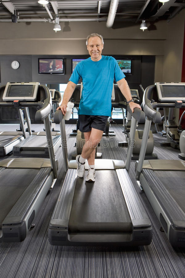 Portrait of smiling man standing on treadmill in health club. Portrait of smiling men standing on treadmill in health club royalty free stock image