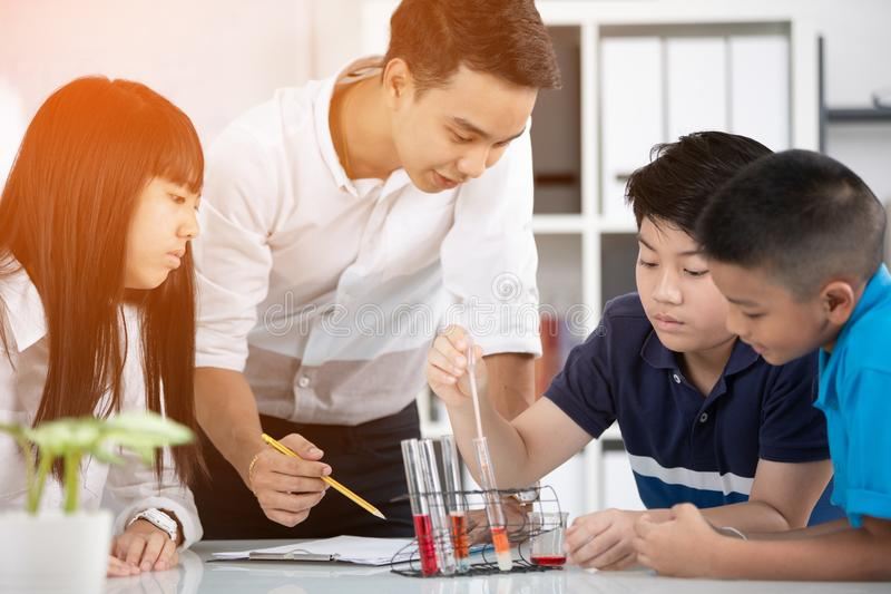 Portrait of smiling man teacher and students scientists making e stock photos