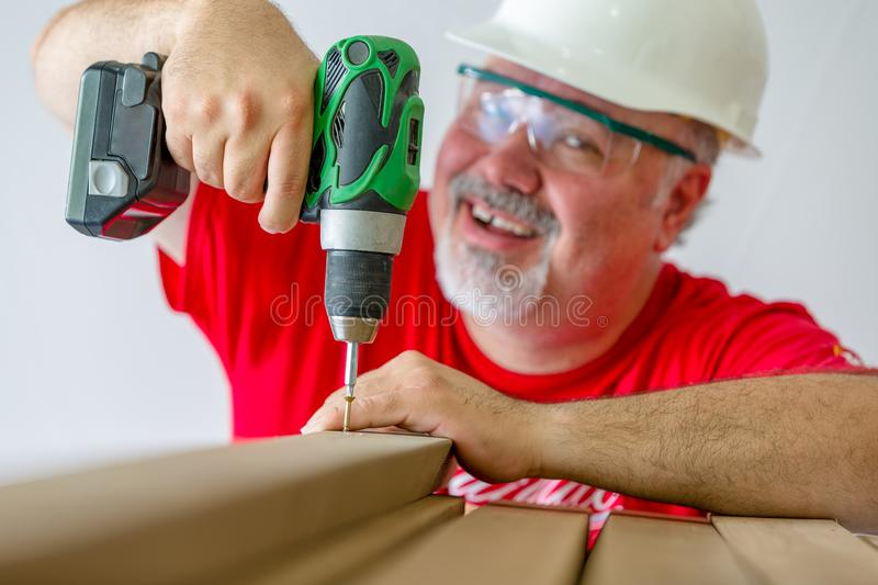 Cheerful worker assembling wood with drill-drive stock photography