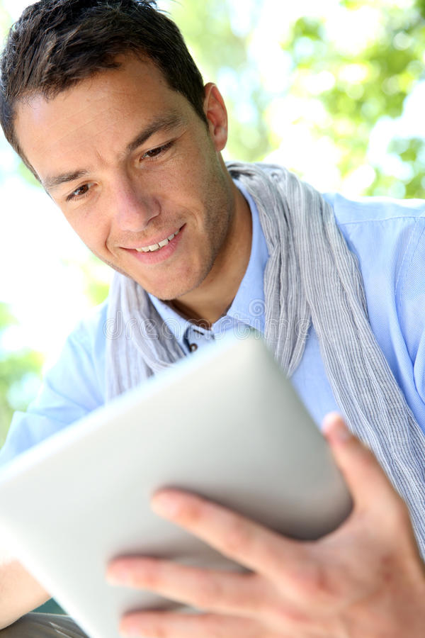 Portrait of smiling man using tablet stock image