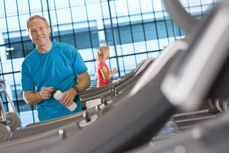 Portrait of smiling man with water bottle leaning on treadmill in health club. Portrait of smiling men with water bottle leaning on treadmill in health club royalty free stock image