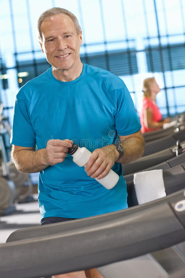 Portrait of smiling man with water bottle leaning on treadmill in health club. Portrait of smiling men with water bottle leaning on treadmill in health club royalty free stock images