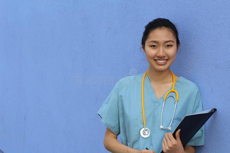 Portrait of smiling mature Asian doctor with stethoscope isolated over blue background with copy space royalty free stock photo