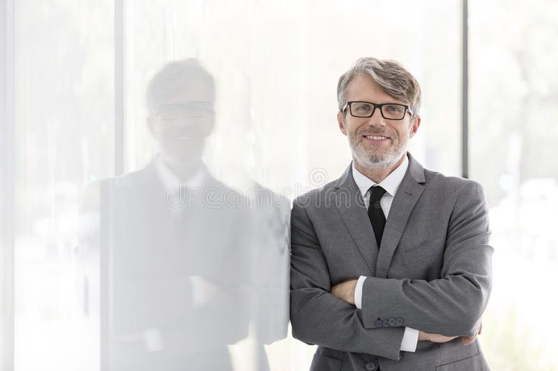 Portrait of smiling mature businessman with arms crossed leaning on wall at office royalty free stock photo