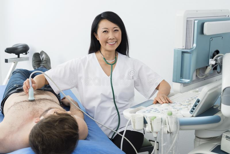 Smiling Doctor Performing Ultrasound Test On Patient In Hospital. Portrait of smiling mature female doctor performing ultrasound test on male patient in hospital stock image