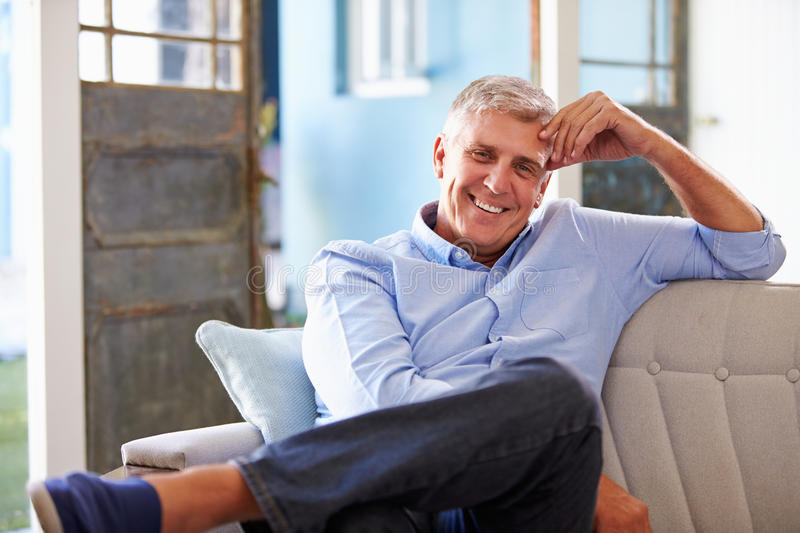 Portrait Of Smiling Mature Man Sitting On Sofa At Home stock photo