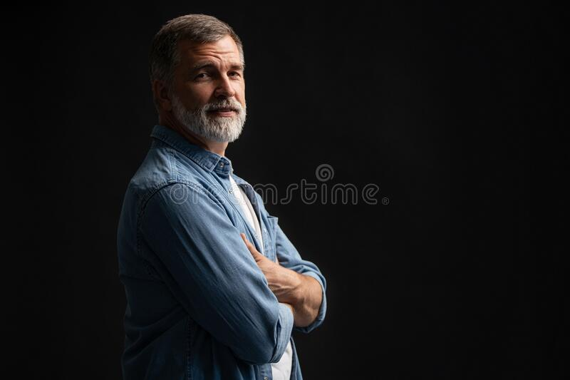 Portrait of smiling mature man standing on black background. royalty free stock image