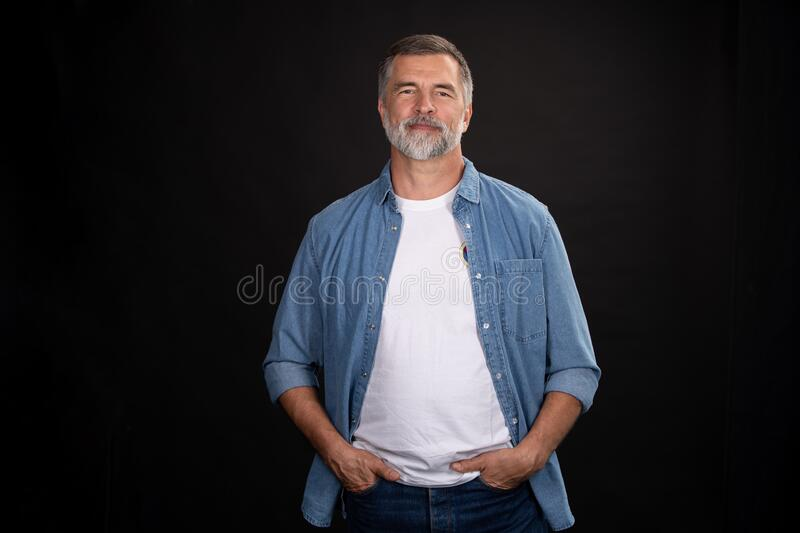 Portrait of smiling mature man standing on black background. stock photo