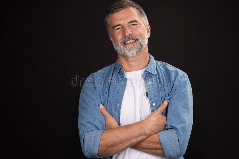 Portrait of smiling mature man standing on black background. stock images