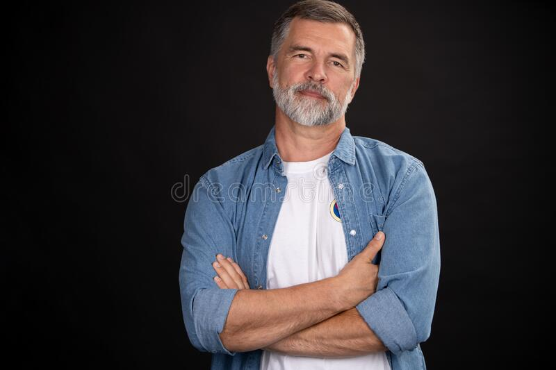 Portrait of smiling mature man standing on black background. stock photos