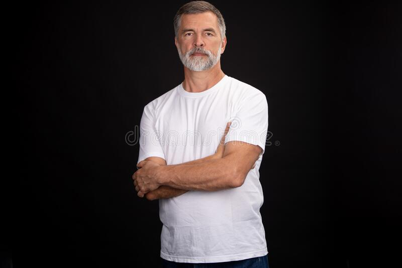 Portrait of smiling mature man standing on black background. royalty free stock photos