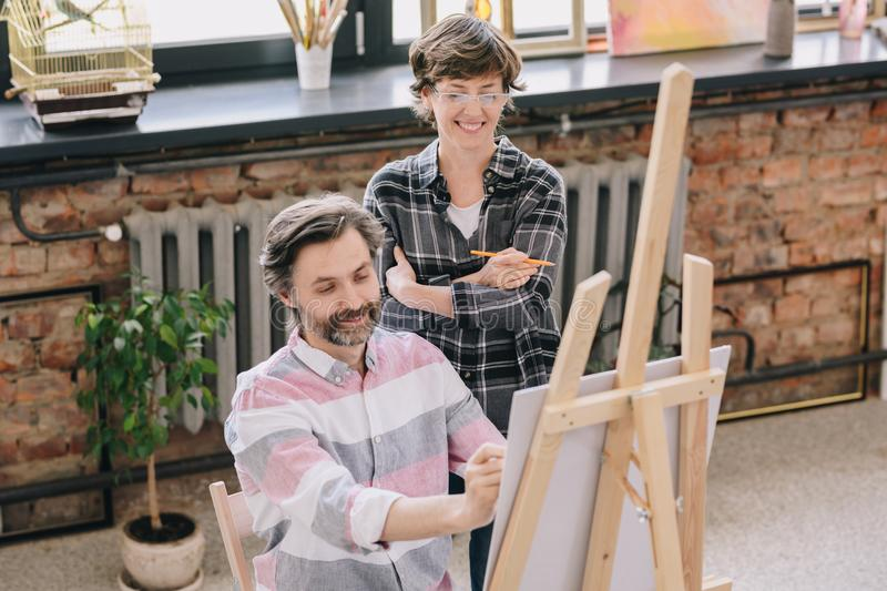 Mature Man Enjoying Art Class. Portrait of smiling mature men painting sitting by easel in art studio with female art teacher watching him in art class, copy stock image