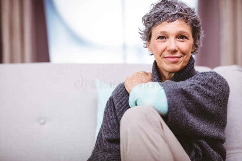 Portrait of smiling mature woman sitting on sofa royalty free stock images