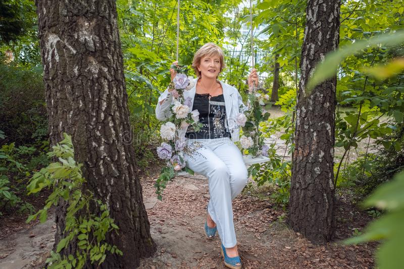 Portrait of a smiling mature woman sitting on swing in the park stock photography
