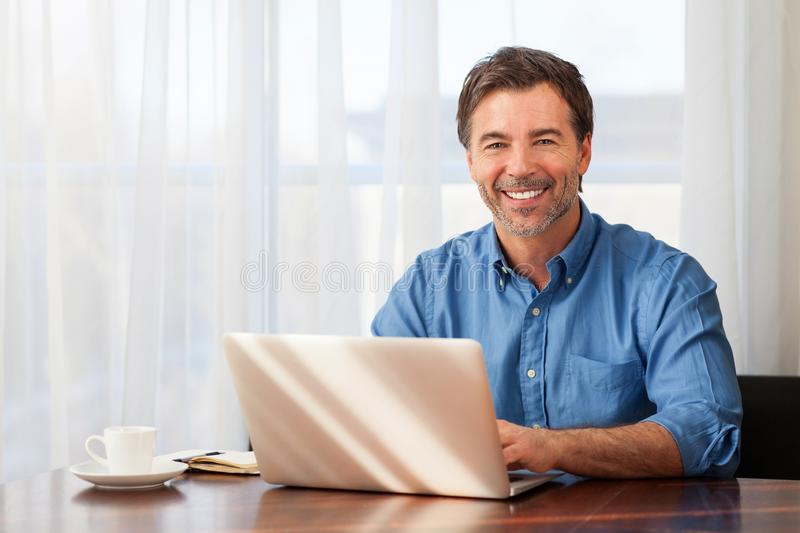 A portrait of a smiling middle-aged bearded man on a window background royalty free stock photo