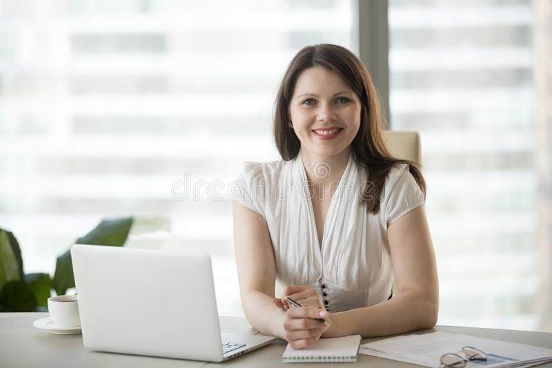 Portrait of smiling confident businesswoman posing for photoshoo. Portrait of smiling middle aged businesswoman working at laptop at office desk, making notes at royalty free stock images