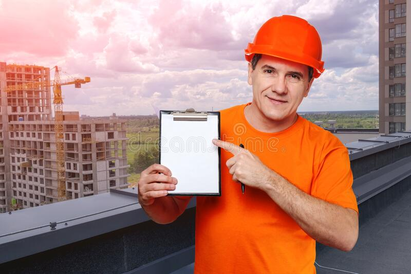 Portrait smiling middle-aged handsome worker wearing orange hard hat, looking to the camera and holding clipboard stock photos
