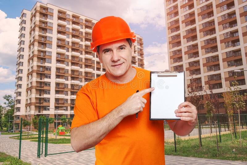 Portrait smiling middle-aged handsome worker wearing orange hard hat, looking to the camera and holding clipboard stock photography
