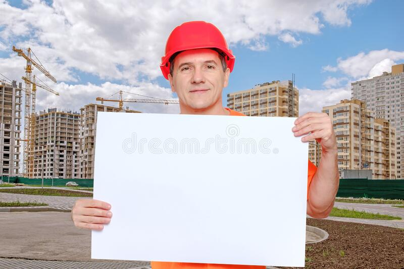 Portrait smiling middle-aged handsome worker wearing red hard hat, looking to the camera and holding blank paper sheet stock image