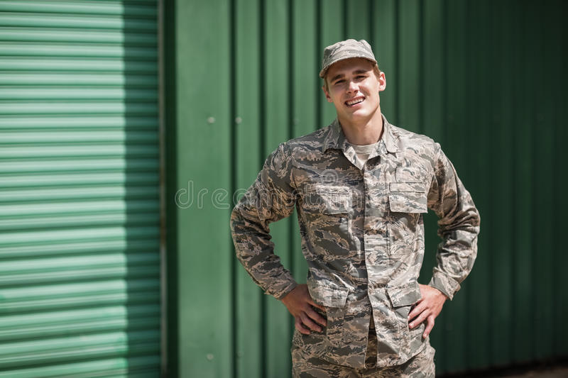 Portrait of smiling military soldier standing with hands on hip stock photo