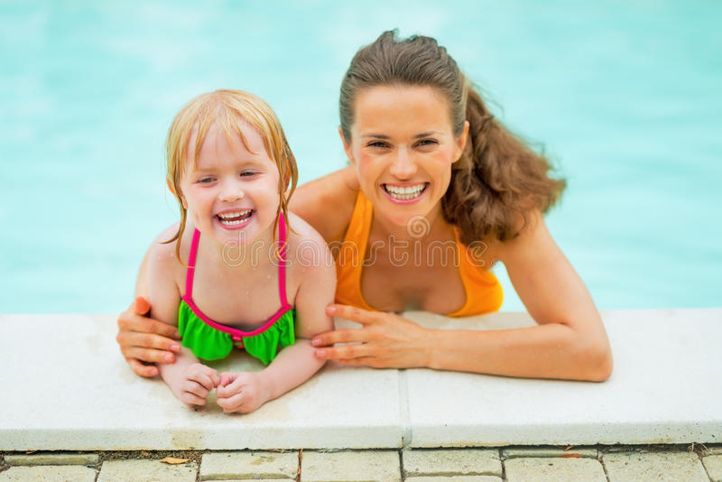Portrait of smiling mother and baby girl in pool royalty free stock images