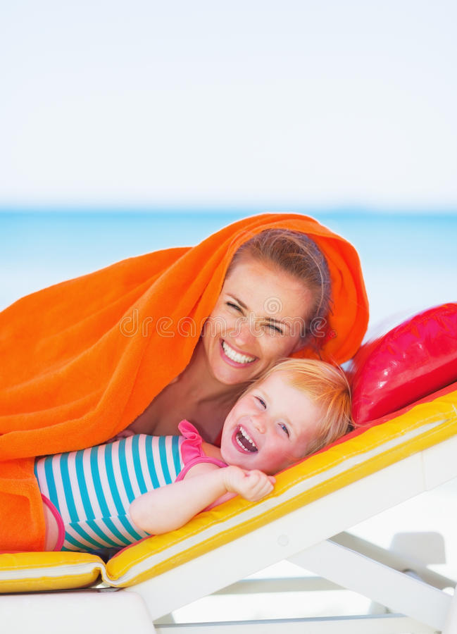 Portrait of smiling mother and baby laying on sunbed. High-resolution photo stock images