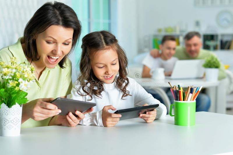 Portrait of smiling mother and daughter sitting at table and using digital tablets stock photo