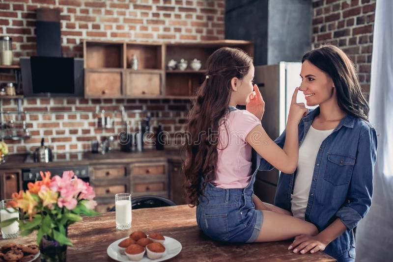 Mother and daughter touching noses with fingers. Portrait of smiling mother and daughter touching noses with fingers on the kitchen royalty free stock images