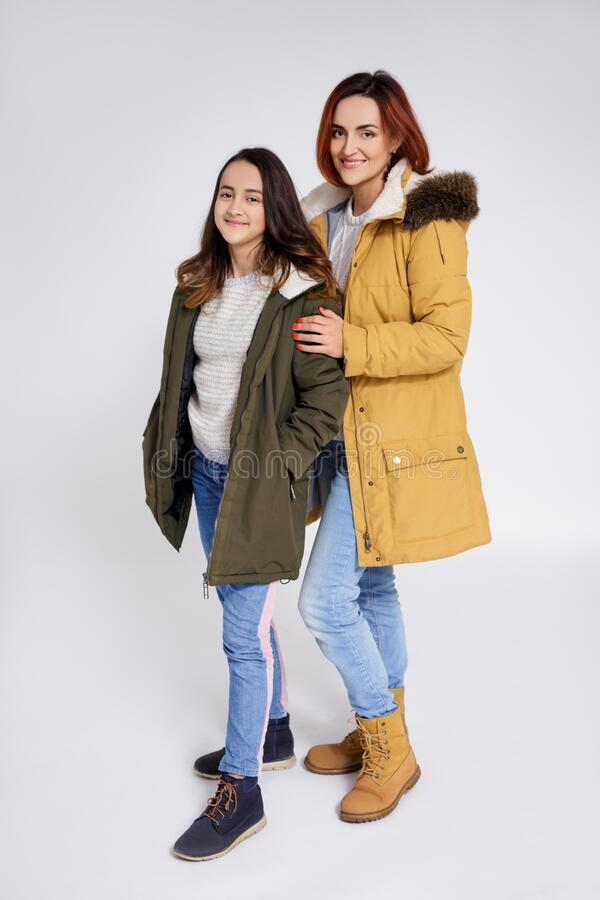 Portrait of smiling mother and daughter in warm winter clothes posing over grey background. Full length portrait of smiling mother and daughter in warm winter stock image