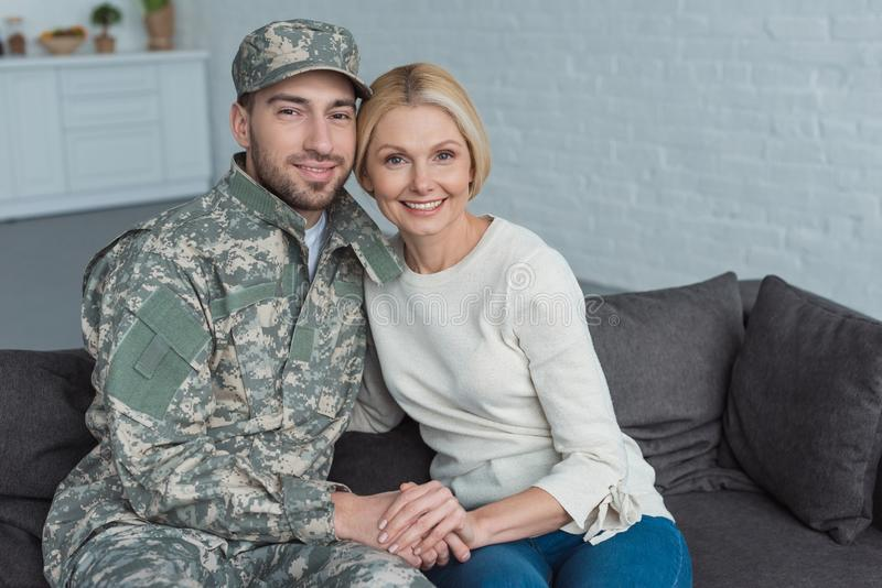portrait of smiling mother and grown son in military uniform holding hands on sofa royalty free stock photography