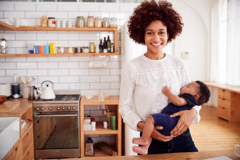 Portrait Of Smiling Mother Holding Sleeping Baby Son In Kitchen stock photos