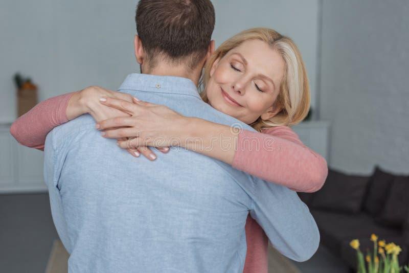 portrait of smiling mother hugging stock image