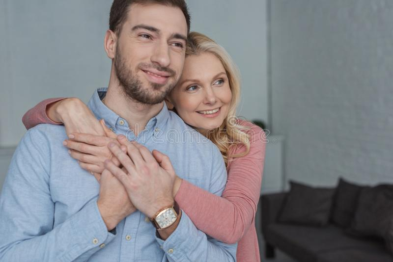 portrait of smiling mother hugging grown son stock images